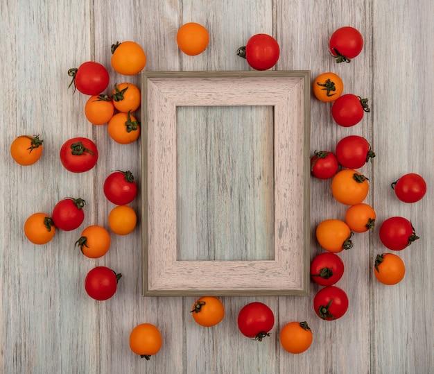 Vista dall'alto di pomodori rossi e arancioni freschi isolati su uno sfondo di legno grigio con spazio di copia