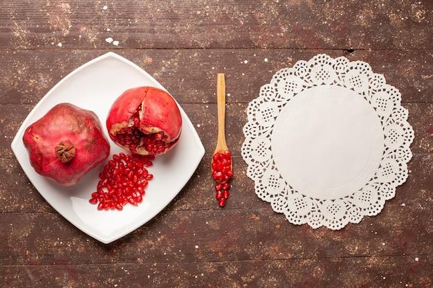 Vista dall'alto melograni rossi freschi all'interno del piatto sullo scrittorio rustico marrone