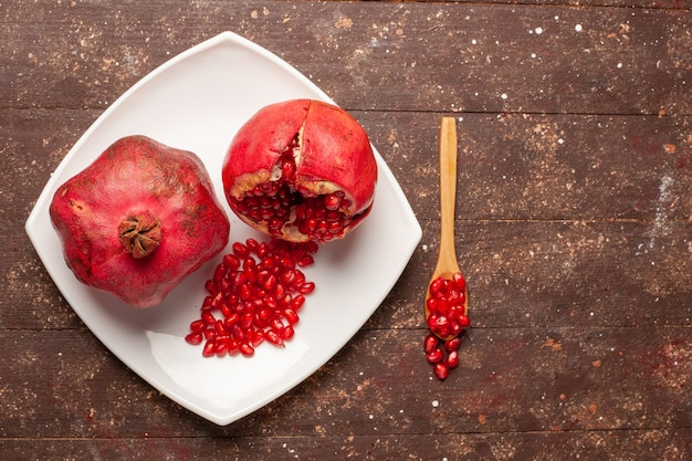 Top view fresh red pomegranates inside plate on the brown rustic desk