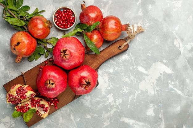 明るい白い机の上に新鮮な赤いザクロの酸っぱくてまろやかな果物の上面図