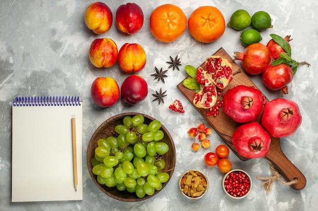 平面図新鮮な赤いザクロ酸っぱくてまろやかな果物と新鮮な緑のブドウが明るい白い机の上に