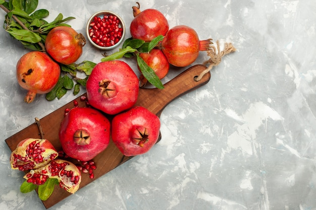 Top view fresh red pomegranates sour and mellow fruits on the light-white desk Free Photo
