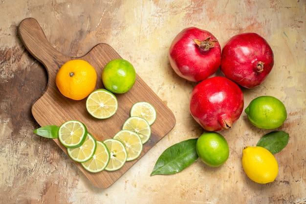 Vista dall'alto di melograni rossi freschi e limoni tagliati interi e tritati sul tabellone su sfondo a colori misti