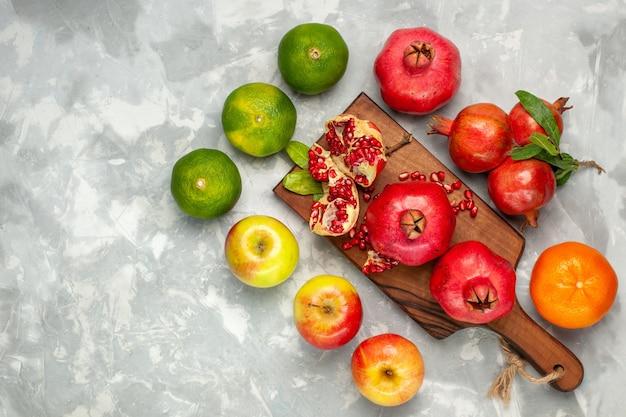 Вид сверху свежие красные гранаты с мандаринами и яблоками на светло-белом столе