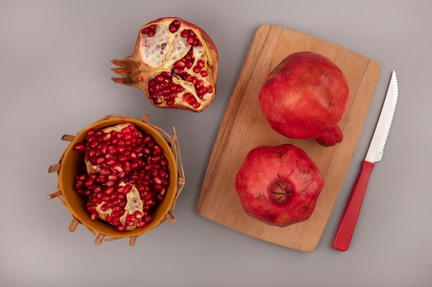 Vista dall'alto di melograni rossi freschi su una tavola di cucina in legno con coltello con semi di melograno su una ciotola