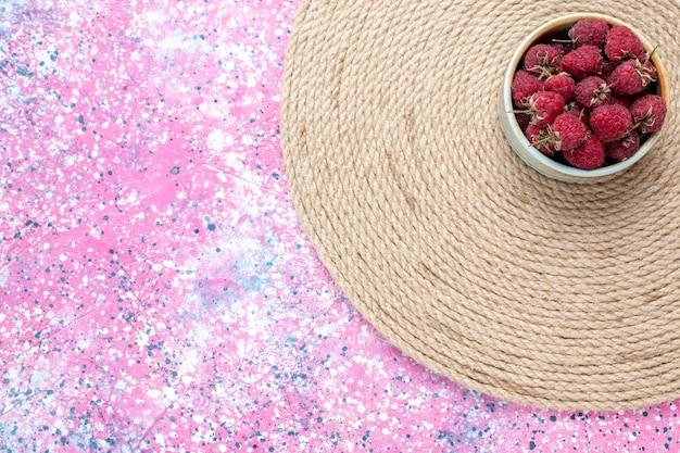 Вид сверху свежие красные малины внутри небольшого горшка на розовом столе.
