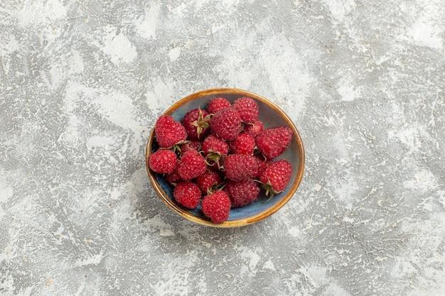 上面図白い背景の上のプレート内の新鮮な赤いラズベリー