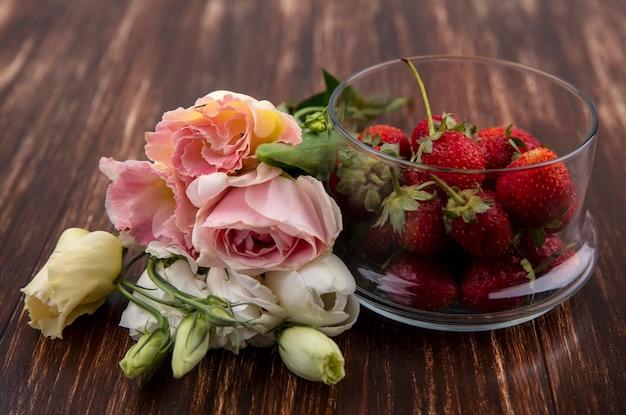 Vista dall'alto di fragole rosse fresche su una ciotola con bellissimi fiori come tulipani e rose su uno sfondo di legno