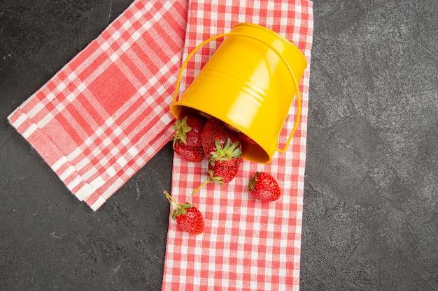 Вид сверху свежей красной клубники внутри корзины на сером столе, цвет малины