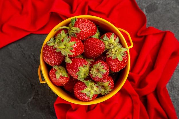 Fragole rosse fresche di vista superiore all'interno del piccolo canestro sulla bacca della frutta della tavola scura