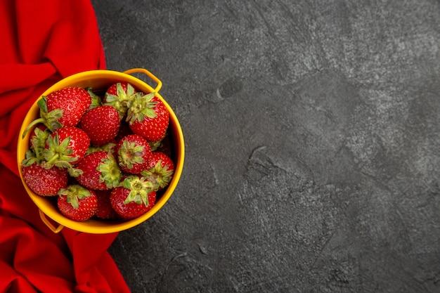 Вид сверху свежей красной клубники в маленькой корзинке на темном столе с фруктовыми ягодами