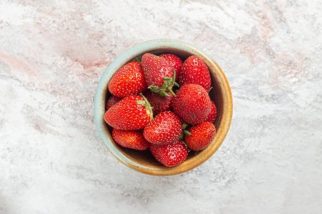 上面図白いテーブルベリーフルーツ野生の小さなプレート内の新鮮な赤いイチゴ
