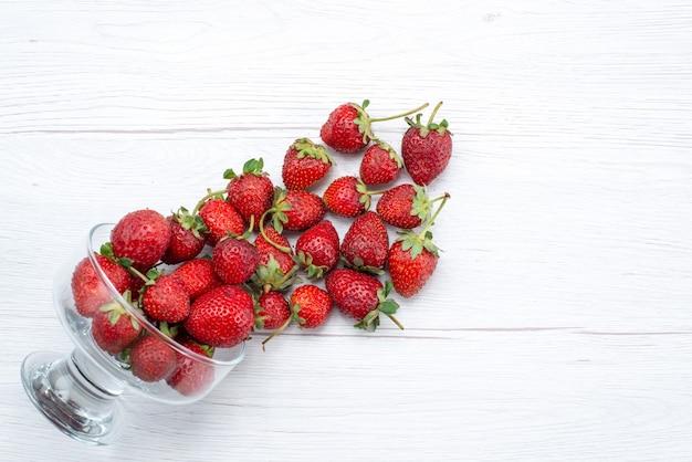 Vista dall'alto di fragole rosse fresche all'interno e all'esterno della piastra su bianco, bacche di frutta fresca mellow