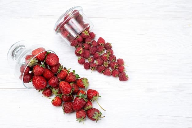 Vista dall'alto di fragole rosse fresche all'interno e all'esterno del piatto su luce bianca, bacche di frutta fresca mellow