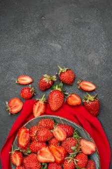 Vista dall'alto fragole rosse fresche all'interno del piatto su sfondo scuro