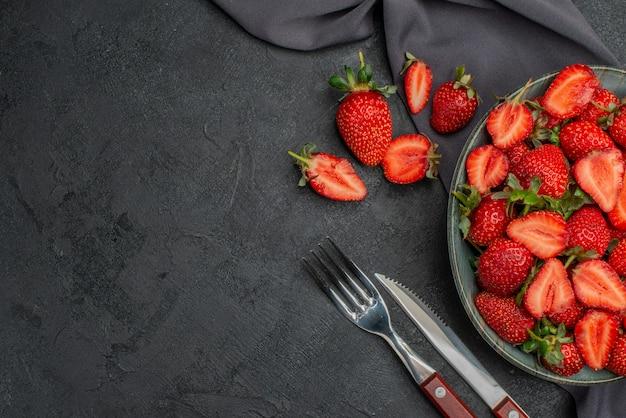 暗い背景のプレート内の新鮮な赤いイチゴの上面図