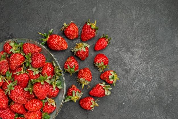 灰色の背景のプレート内の新鮮な赤いイチゴの上面図