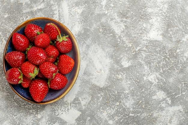 Вид сверху свежей красной клубники внутри тарелки на белом фоне