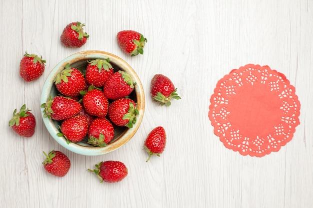 白い机の上のプレート内の新鮮な赤いイチゴ