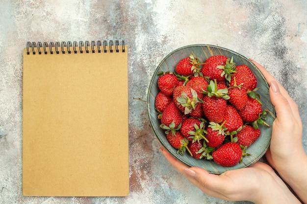 Vista dall'alto fragole rosse fresche all'interno del piatto su sfondo bianco