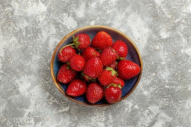 Vista dall'alto fragole rosse fresche all'interno della piastra su sfondo bianco