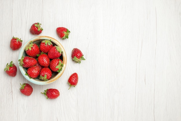 Top view fresh red strawberries inside plate on white desk