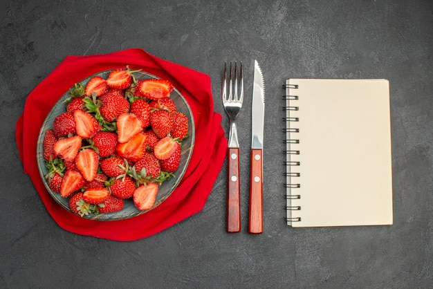 Vista dall'alto fragole rosse fresche all'interno del piatto con posate su uno sfondo scuro