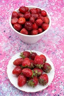 色付きの背景のフルーツベリー色ビタミンの白いプレート内のトップビュー新鮮な赤いイチゴ