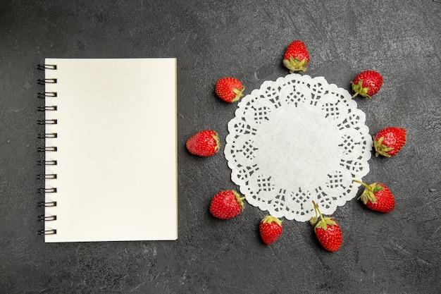 Vista dall'alto fragole rosse fresche foderate su frutti di bosco di colore tavolo scuro