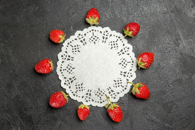 Top view fresh red strawberries lined on dark table color berry fruit