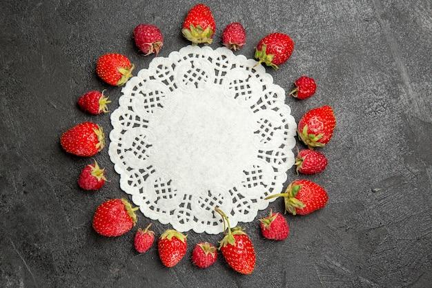 Vista dall'alto fragole rosse fresche foderate su frutti di bosco colore tavolo scuro