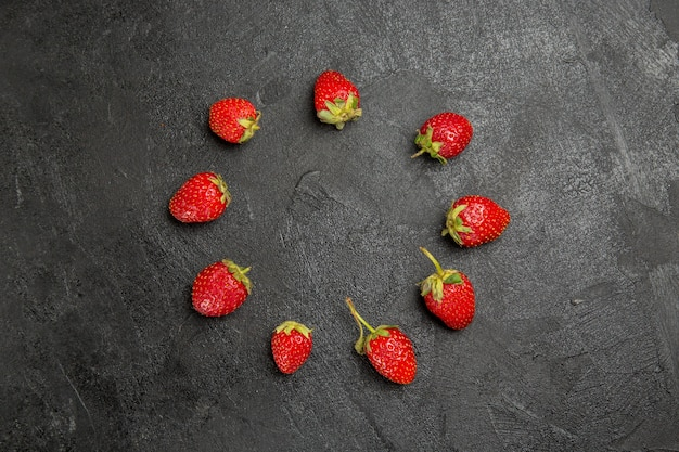 暗いテーブルの色のフルーツベリー熟した上に並んでいる上面図新鮮な赤いイチゴ