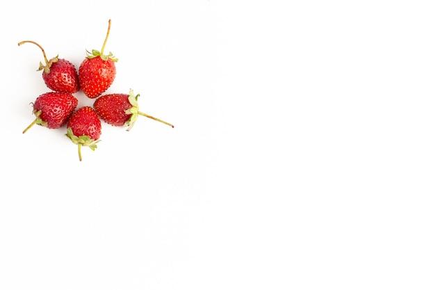 平面図、白い机の上の新鮮な赤いイチゴのまろやかでジューシー
