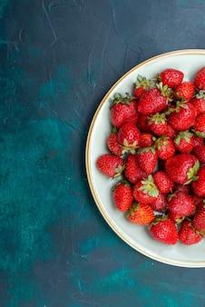Vista dall'alto fragole rosse fresche frutti di bosco bacche all'interno della piastra sulla superficie blu scuro frutti di bosco mellow summer