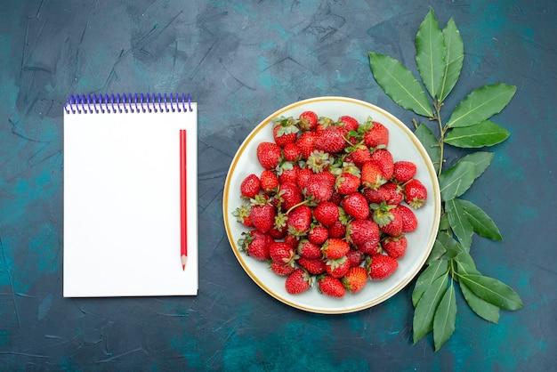 Vista dall'alto fresche fragole rosse mellow frutti bacche all'interno della piastra con blocco note su sfondo blu scuro frutti di bosco mellow summer vitamina cibo maturo
