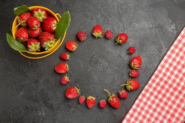 暗いテーブルの上の新鮮な赤いイチゴの上面図ベリー色フルーツラズベリー
