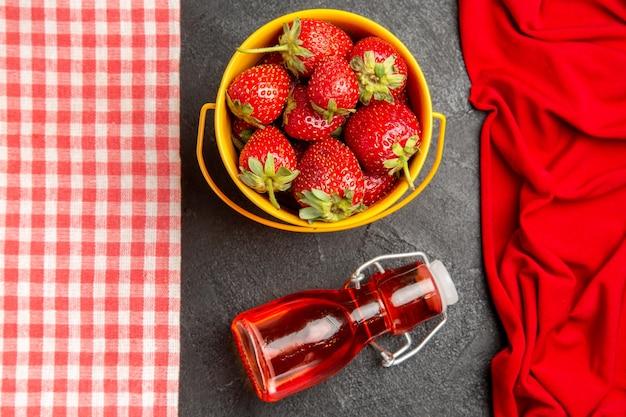 Вид сверху свежей красной клубники на темном столе с фруктовыми ягодами малины