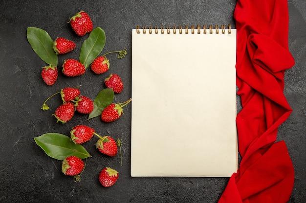 暗いテーブルの上の新鮮な赤いイチゴの上面図フルーツベリー熟した色