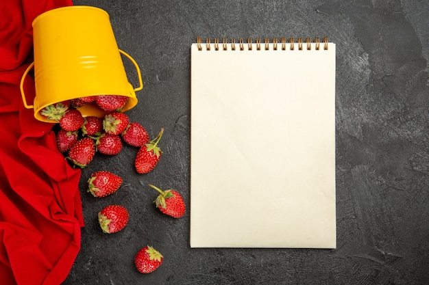 Вид сверху свежей красной клубники на темном столе, спелые ягоды
