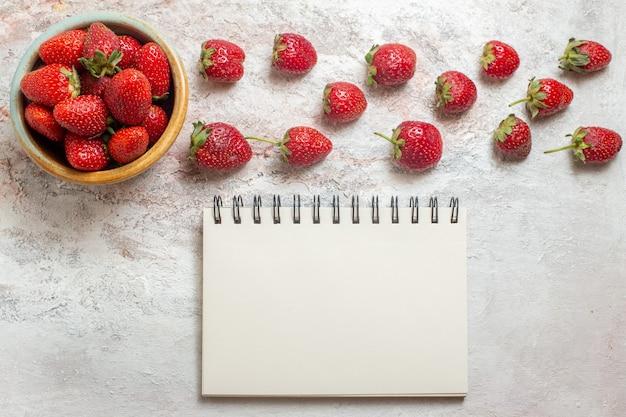 Fragole rosse fresche di vista superiore sulla tavola bianca frutta rossa fresca