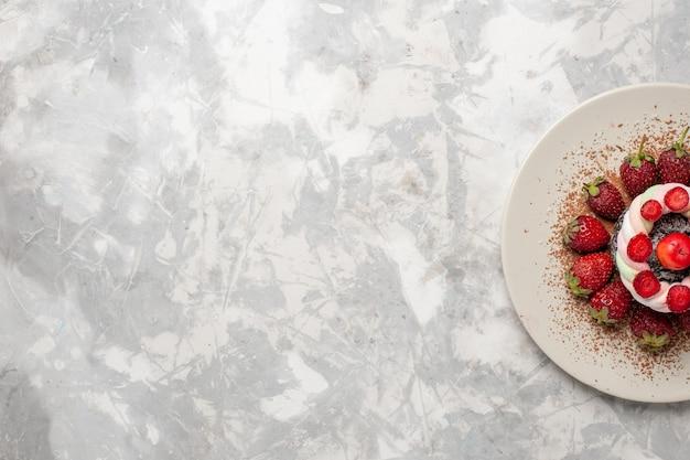 Vista dall'alto fragole rosse fresche con torta su uno spazio bianco chiaro