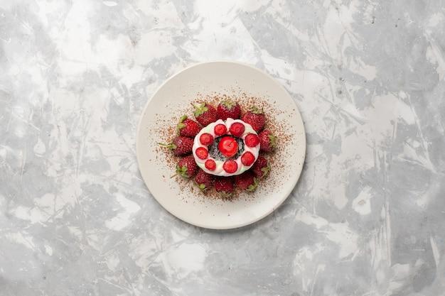 Вид сверху свежей красной клубники с тортом на белом пространстве