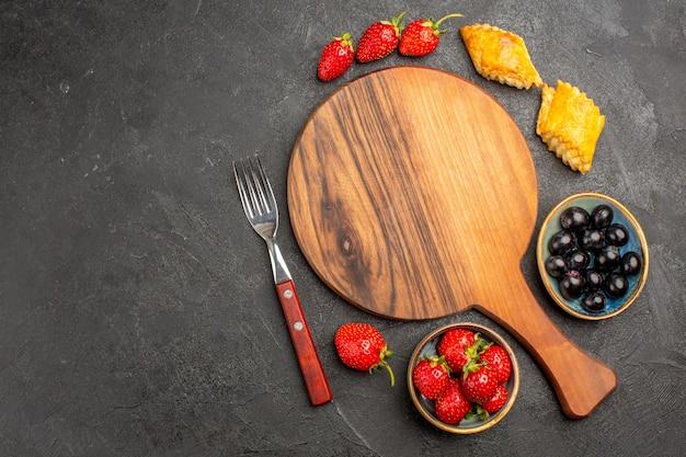 Вид сверху свежей красной клубники с тортами и оливками на темной поверхности ягодных свежих фруктов
