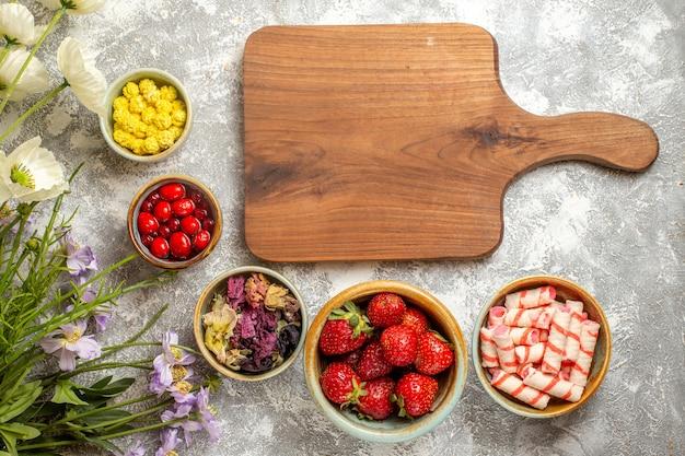 흰색 표면 신선한 사탕 베리 과일에 사탕과 상위 뷰 신선한 빨간 딸기