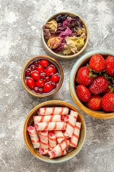 흰색 표면 베리 과일 빨간 사탕에 사탕과 상위 뷰 신선한 빨간 딸기