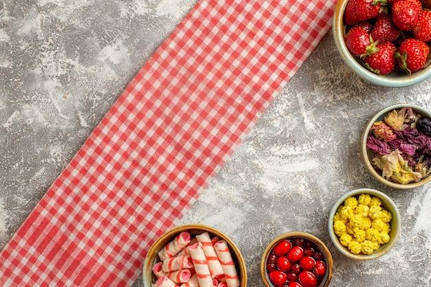 Вид сверху свежей красной клубники с конфетами на белой поверхности ягодных свежих конфет