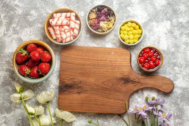 흰색 표면 베리 과일 사탕에 사탕과 상위 뷰 신선한 빨간 딸기