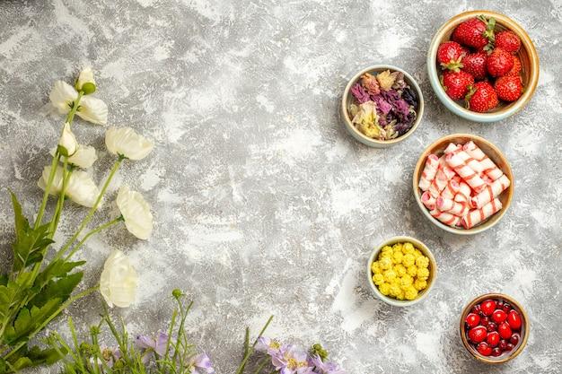 上面図白い表面のフルーツゼリーの花にキャンディーと新鮮な赤いイチゴ