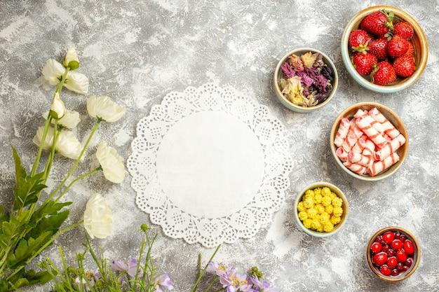 흰색 표면 과일 젤리 꽃에 사탕과 상위 뷰 신선한 빨간 딸기