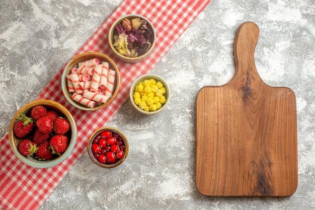 Fragole rosse fresche di vista superiore con le caramelle sulla frutta fresca della caramella della bacca del pavimento bianco